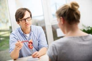 Osteopath Dr. Teichgräber erklärt Patienten mit Ohrmodell Zusammenhänge im Körper