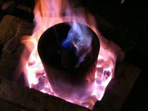 Das Bild zeigt ein Gefäß in einem Ofen, Kohle und Feuer