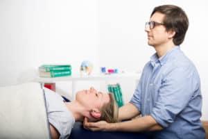 Das Bild zeigt Dr. Teichgräber und eine junge Frau während einer Behandlung mit Cranio Sacral Therapie. Der Arzt sitzt und die Frau liegt. Dabei hält der Arzt die Finger am Kopfgelenk der Frau.